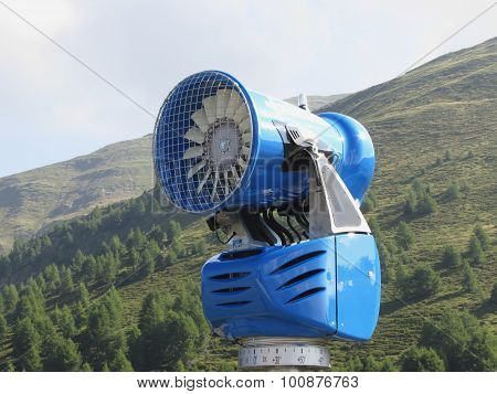 Snow Cannon With Mountains Background In Summertime . Sesto Dolomites, South Tyrol, Italy