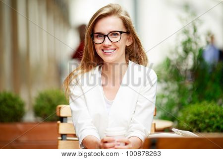 Portrait of a smiling business woman, sitting in a street cafe