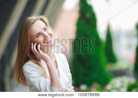 Young pretty woman with mobile phone. City defocusrd background.