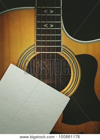 acoustic guitar with the clean sheet of paper on a dark background