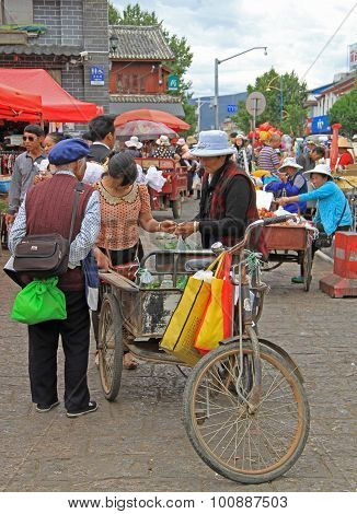 woman is selling goods from body of tricycle in Lijiang, China