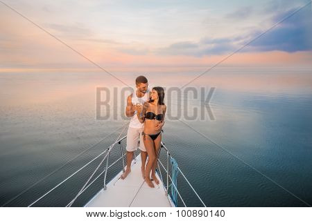 Guy with  girl drink champagne on the ship.