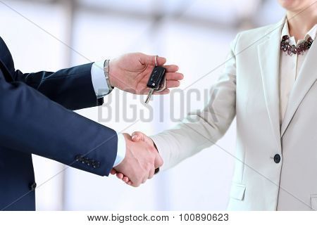 Car Saleswoman Handing Over The Keys For A New Car To A Young Businessman . Handshake Between Two Bu