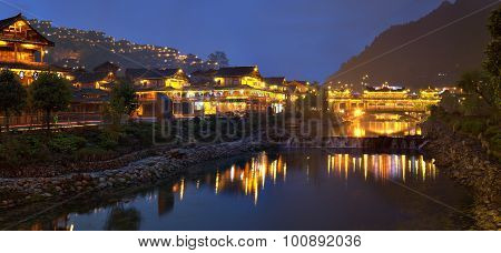 Night Lights Of Big Chinese Village, Reflected In River Water.