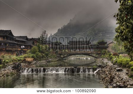 Dam On Rural River And Covered Carved Wooden Bridge, China.