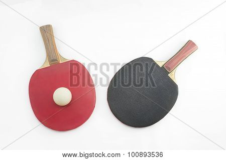 Two Table Tennis Rackets And A Ball On White