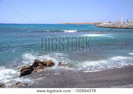Picturesque black pebble beach in Las Galletas on the south of Tenerife, Spain