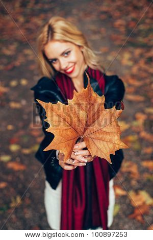 Beautiful Blonde With Leaf In Front Of Face. Selective Focuc On Leaf.