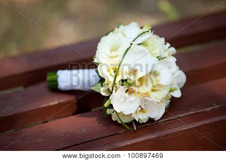 White and yellow bouquet on a wooden bench