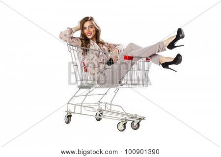 Happy young beautiful brunette woman sits in an empty shopping cart, isolated on white background