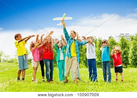 Kid holding white airplane toy and children behind