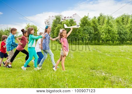 View of girl holding airplane toy and kids behind