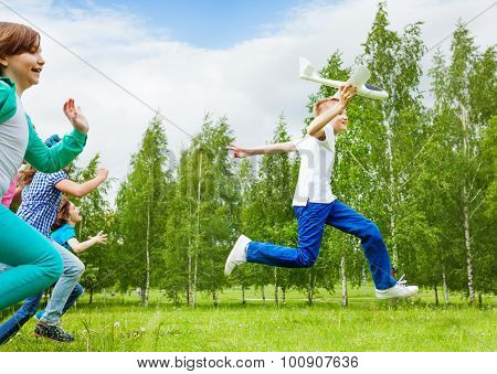 Jumping boy with white airplane toy and children