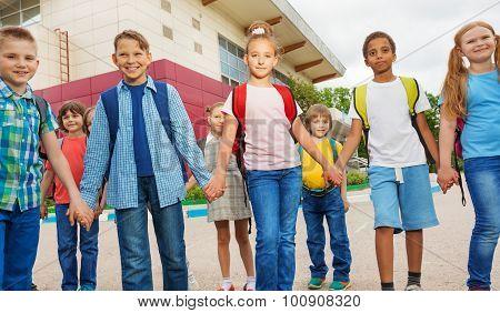 Friends with rucksacks walk near school building