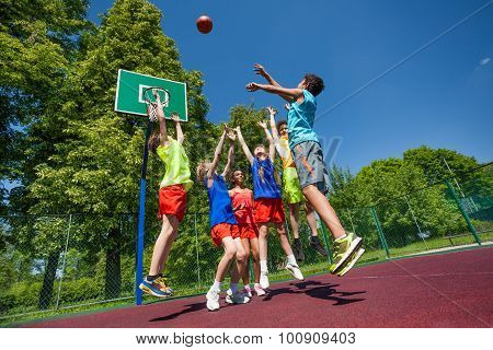 Jumping for ball teenagers playing basketball game