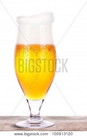Frosty glass of light beer on a wooden table