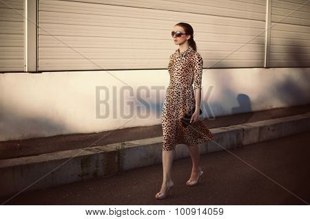 Fashion Young Woman Wearing A Leopard Dress And Handbag Clutch Walking Evening In The City