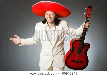 Young mexican guitar player wearing sombrero