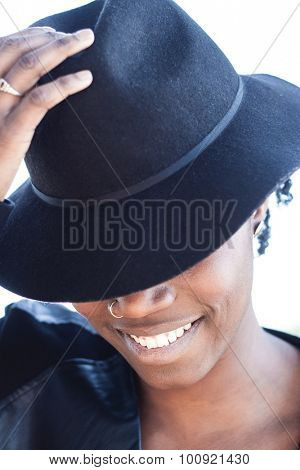 Stylish African woman with a lovely smile doffing her trendy black hat with her hand concealing her upper face with the brim, close up head and shoulders on white