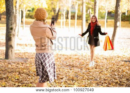 Two women taking photos in the autumn after shopping.