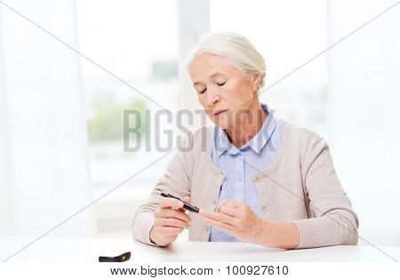 medicine, age, diabetes, health care and people concept - senior woman with glucometer checking blood sugar level at home