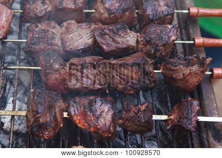 fresh raw beef fillet steak red meat brisket on skewers barbecue brazier grid full burned charcoal