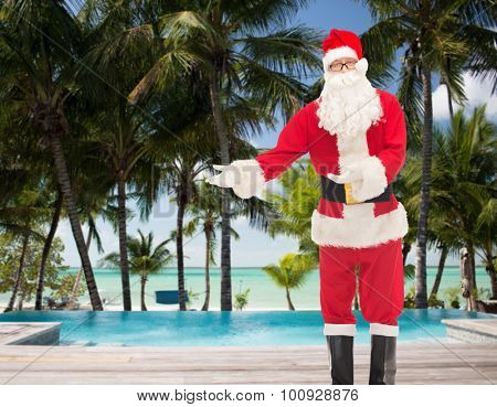christmas, holidays, gesture, travel and people concept - man in costume of santa claus over swimming pool on tropical beach background