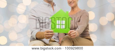 family, relations, real estate, age and people concept - close up of happy senior couple with green paper house cutout over lights background