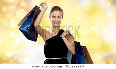 luxury, advertisement, holydays and sale concept - smiling woman with shopping bags over yellow lights background