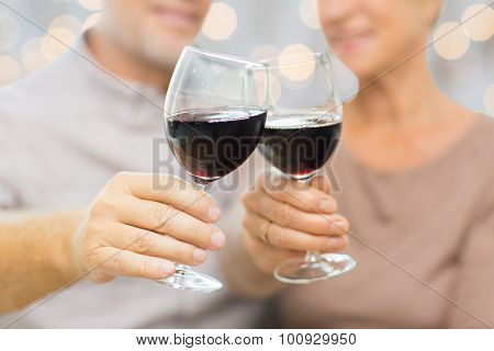 family, holidays, drinks, age and people concept - close up of happy senior couple clinking glasses with red wine over lights background