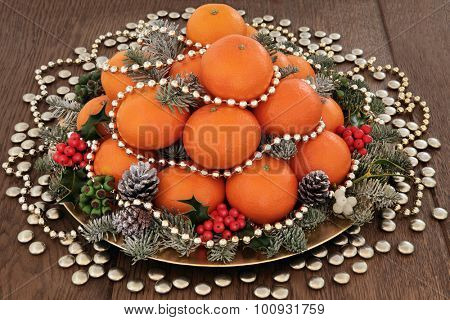 Christmas orange fruit with gold beads and balls, holly, mistletoe, ivy and spruce pine fir with snow over oak background.