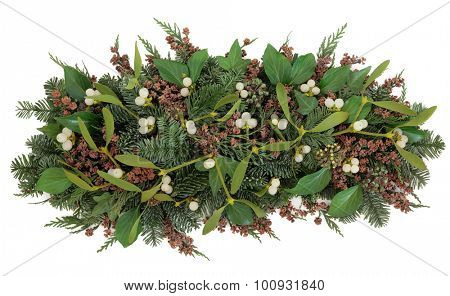 Mistletoe and winter greenery of ivy, blue spruce and cedar cypress leyland leaves with pine cones over white background.