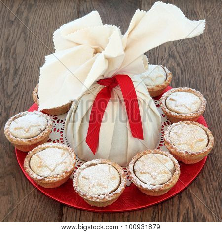 Christmas pudding in a muslin bag with mince pies over oak background.