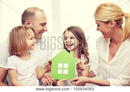 family, children, accommodation and home concept - smiling parents and two little girls at home with green house symbol
