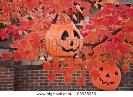 two jack-o-lantern baskets in autumn tree with brick wall