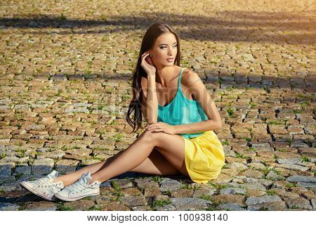 Attractive young woman in casual summer clothes sitting on a paved road.  Fashion shot.