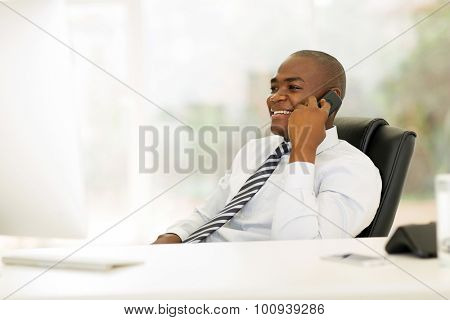 happy african business executive talking on landline