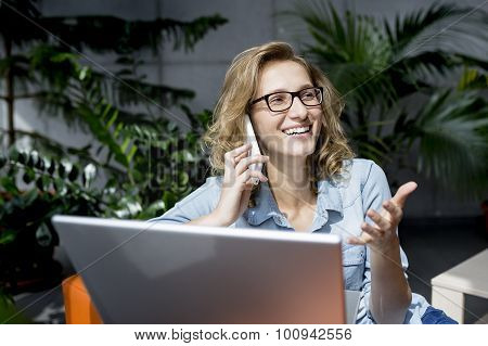 Beautiful young businesswoman using mobile phone while working at laptop.
