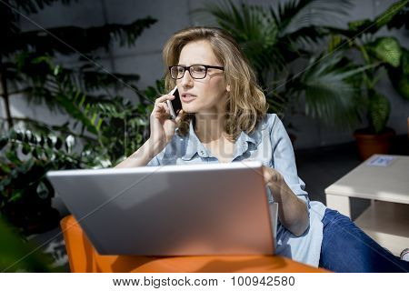 Young businesswoman using mobile phone while working with laptop