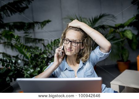 Young businesswoman using mobile phone while working