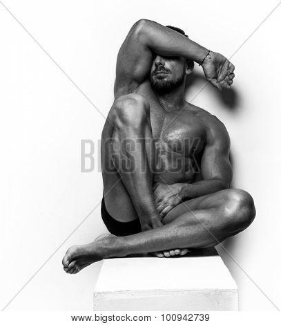 Muscular Man sitting on white steps