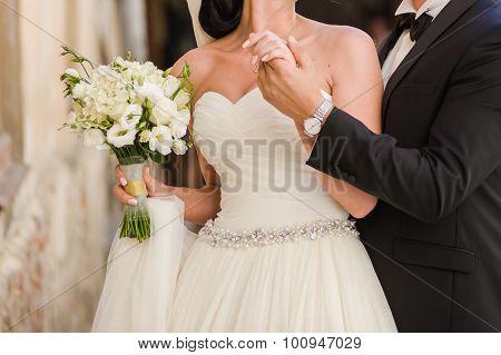 Bride in wedding dress. Groom hugs bride. Big wedding bouquet.