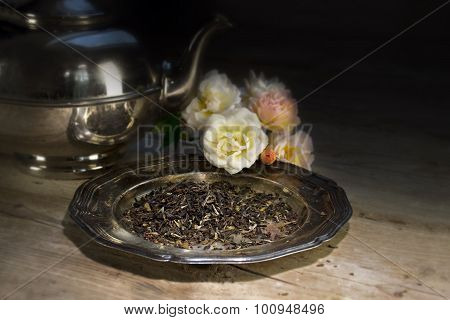 Loose Black Tea On An Old Dish, Roses And Silver Teapot On A Rustic Wooden Table, Dark Blurred Backg