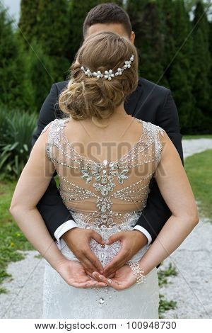 Groom making a heart sign with his hands while holding arms around his bride