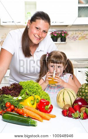 Beautiful Young Woman Gives To The Little Girl Orange Juice  In The Kitchen.