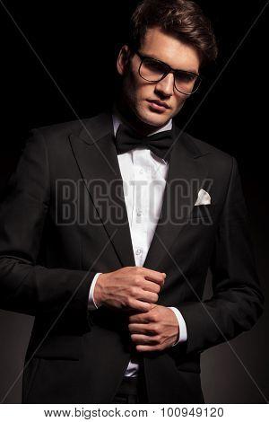 Handsome elegant man closing his jacket while looking at the camera.