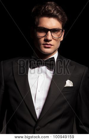 Portrait of a elegant young man wearing a tuxedo and glasses.