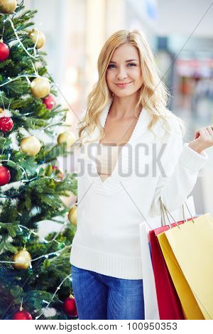 Happy blond woman with paperbags standing by decorated firtree
