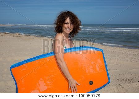 Woman  Having Fun Bodyboarding Under Sun And Blue Sky