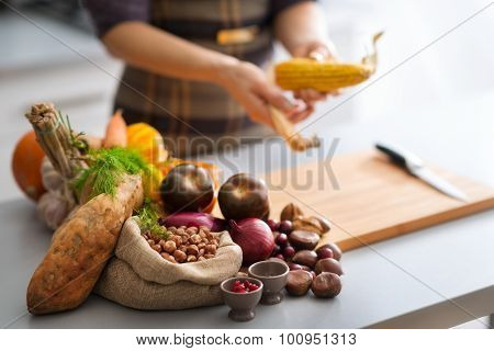 Autumn Vegetables In A Kitchen With Anonymous Woman Husking Corn